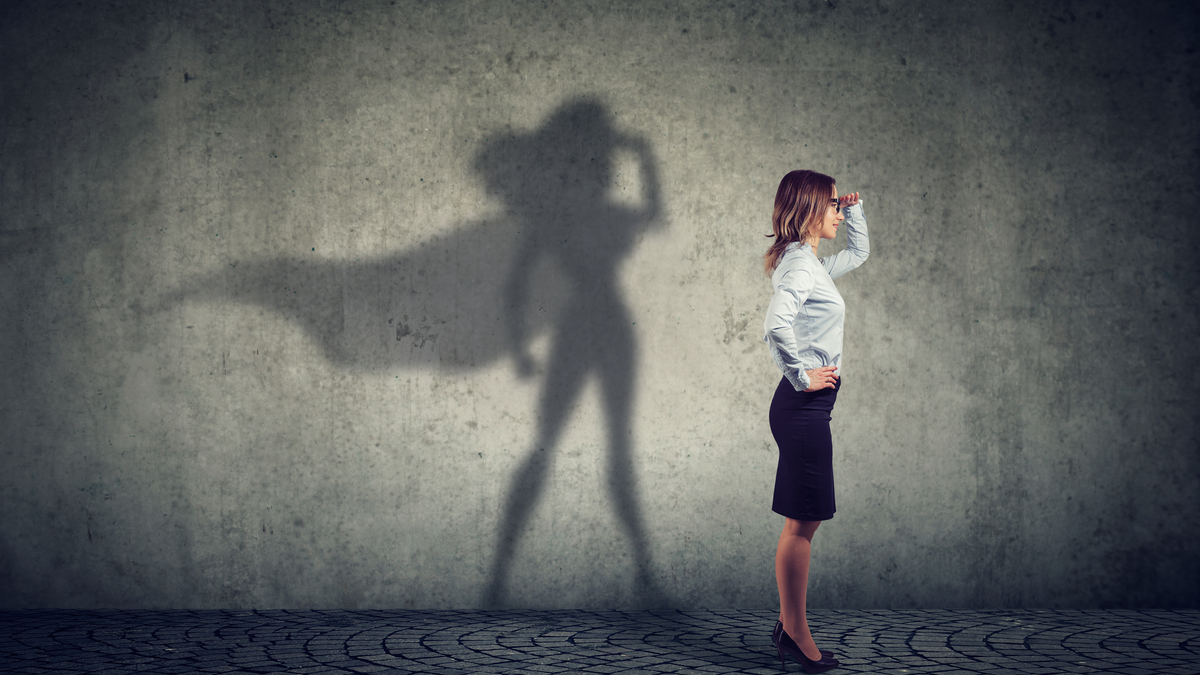Photo illustration of business woman casting shadow as a superhero with a cape