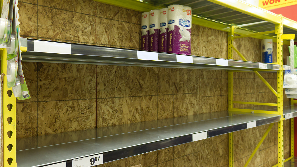 PHoto of nearly empty store shelves with a few rolls of toilet paper