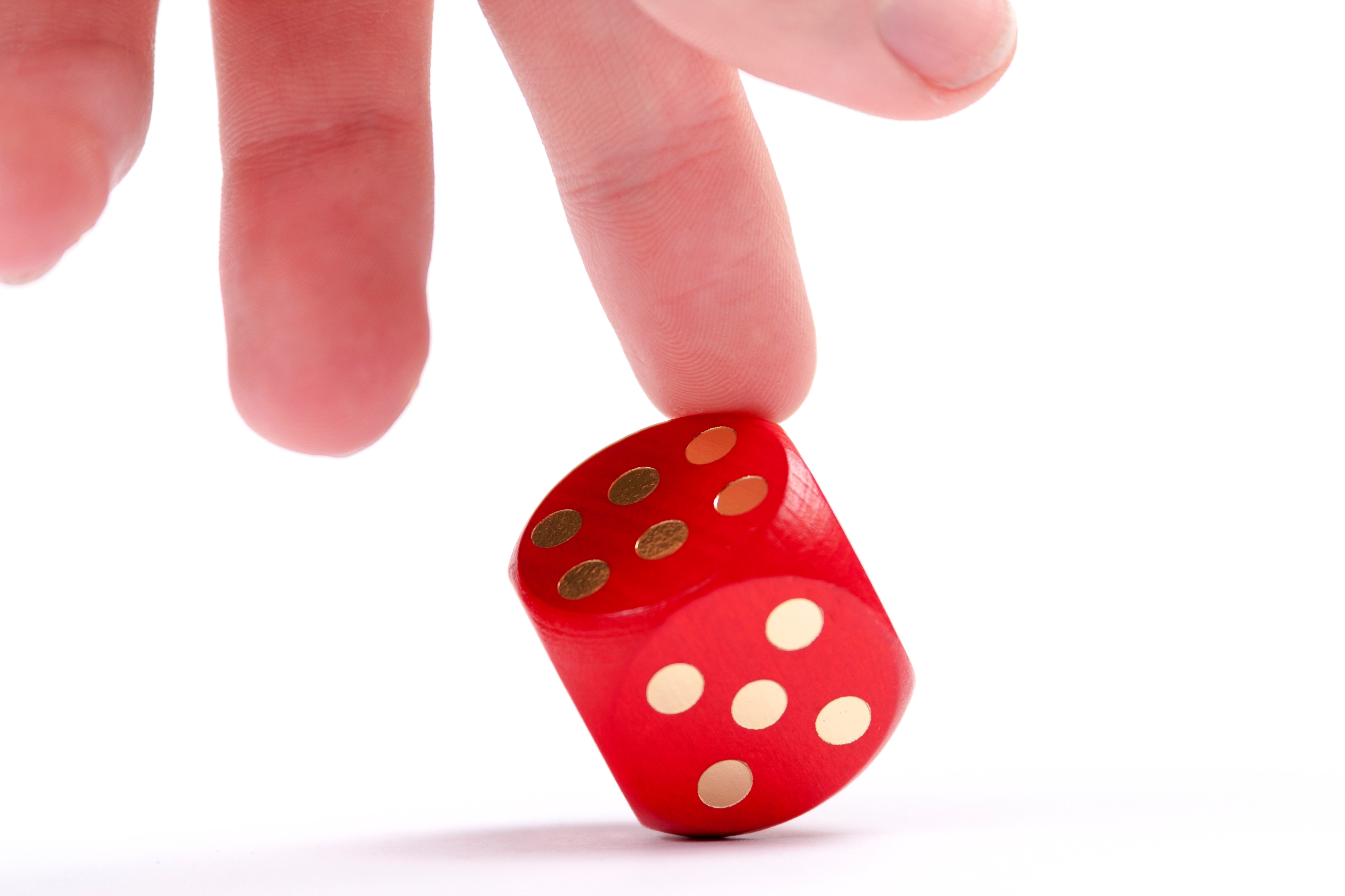 Photo illustration of six-sided die and a hand changing the roll