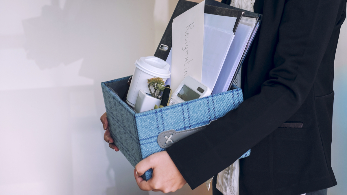 Photo illustration of woman walking with box full of items from desk