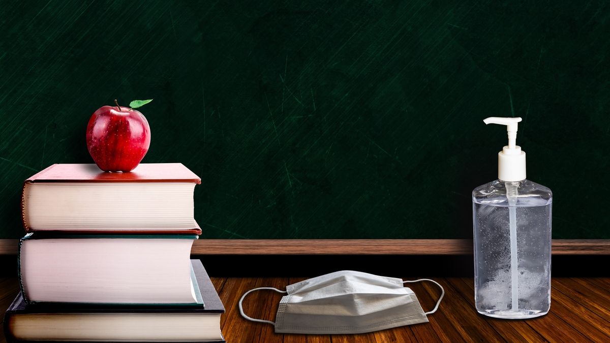 Photo illustration of school books, apple, face mask, and hand sanitizer