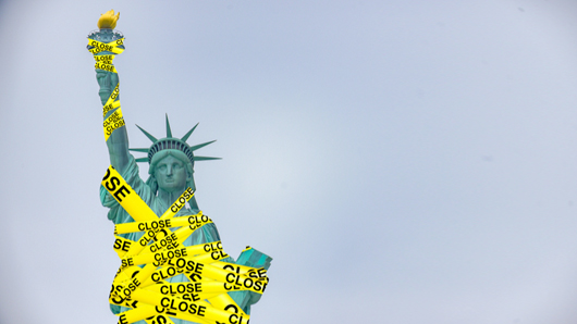 Statue of liberty wrapped in yellow caution tape