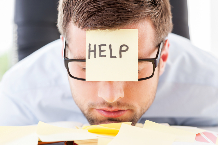 "Man at desk with sticky note reading ""Help"" on his forehead"
