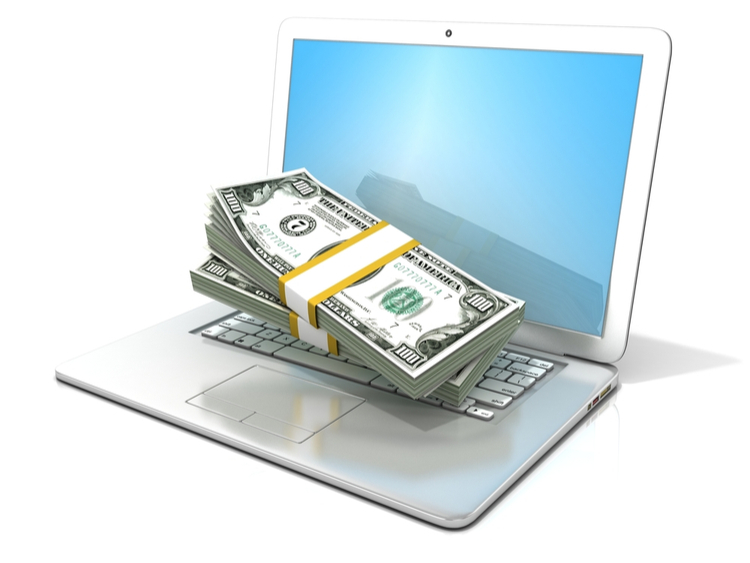 Laptop with pile of money