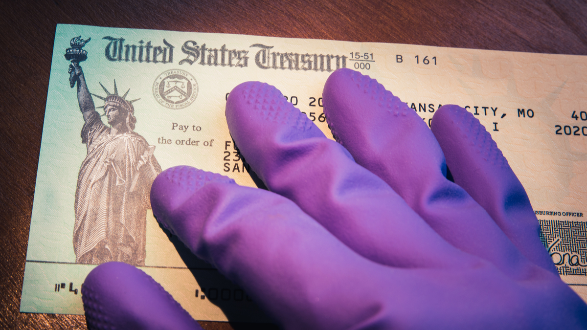 Photo illustration of hand in sanitary glove holding check from U.S. Treasury