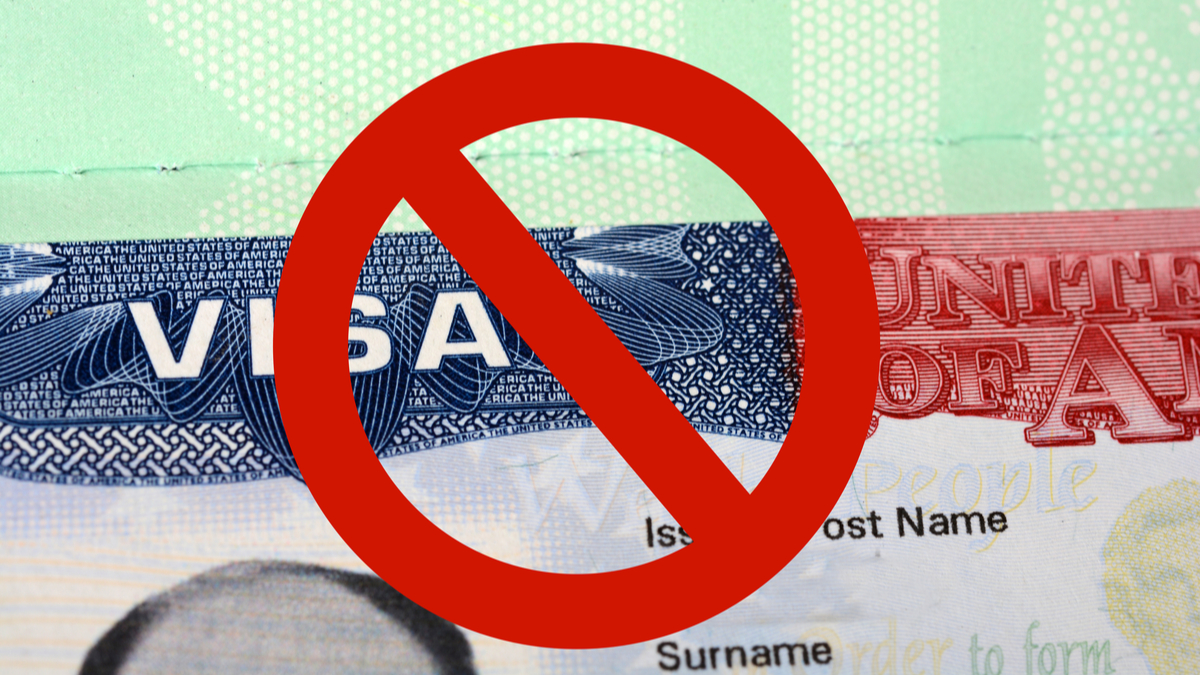 Photo illustration of passport with visa and ban symbol