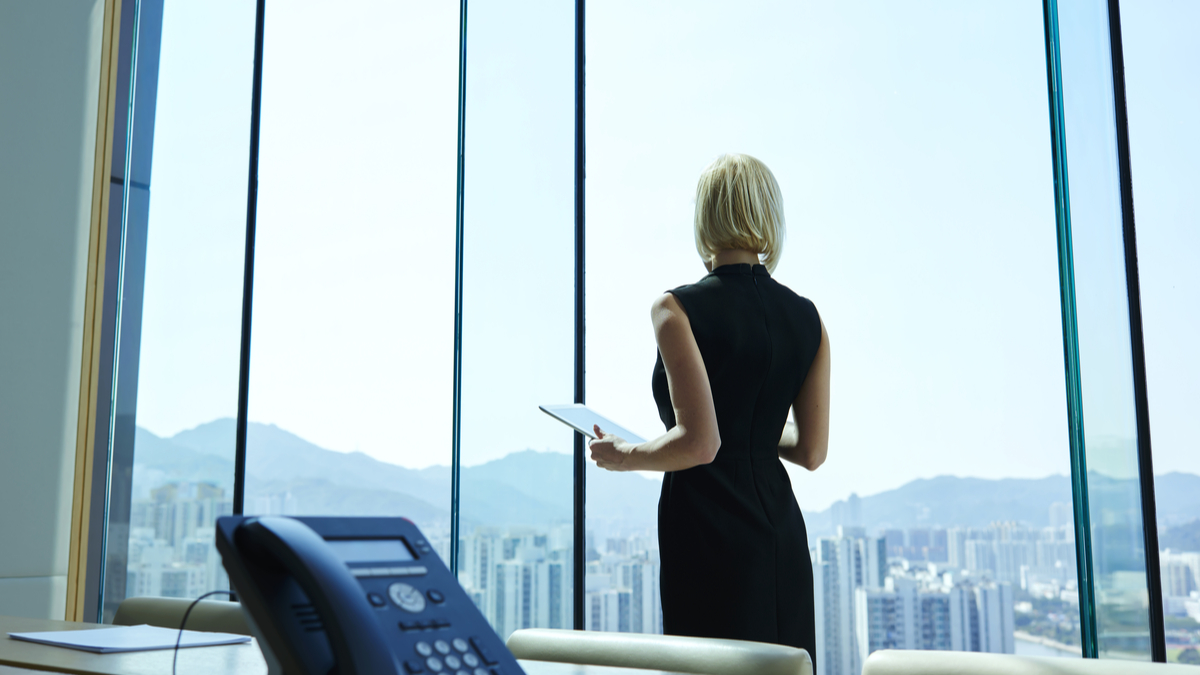 Photo illustration of woman in executive boardroom looking out window over city