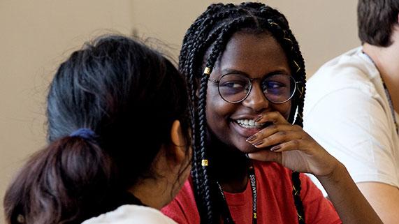 Two diverse women talking in classroom