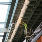A worker installs steel anchor brackets for the new terracotta exterior on Kresge Hall.