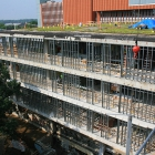 Walls are framed at Kresge Hall. The above photo includes a view of Kresge's green roof, which benefits the environment by providing energy-saving insulation, filtering rainfall and preventing runoff, and improving air quality.