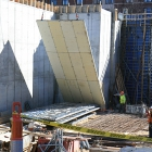 Construction workers lift basement wall formwork into place in March 2015.