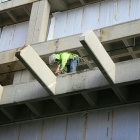 A construction worker completes prep work on the south face of Kresge Hall.