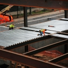 Workers lay down steel for the future floors of the new Jeff T. Blau Hall.